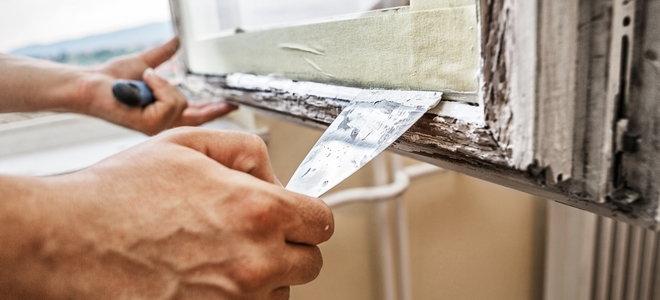 руки с помощью шпателя глазурируют конопатку на старом окне