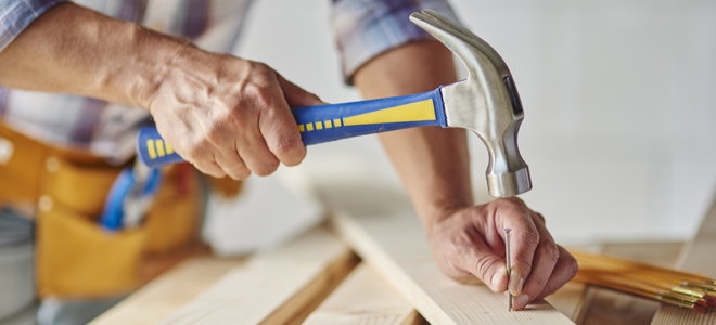 person hammering a nail into a thin board