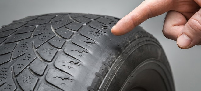 finger pointing at worn tire toe