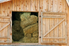 a stack of hay inside a barn with the door open