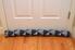 Door draft stopper lying on a wood floor next to a white door.