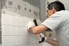 man installing white tile on the wall of a shower