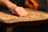 a hand sanding a wooden table