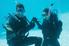 man proposing to woman underwater in scuba gear