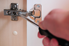 Screwdriver against a cabinet hinge