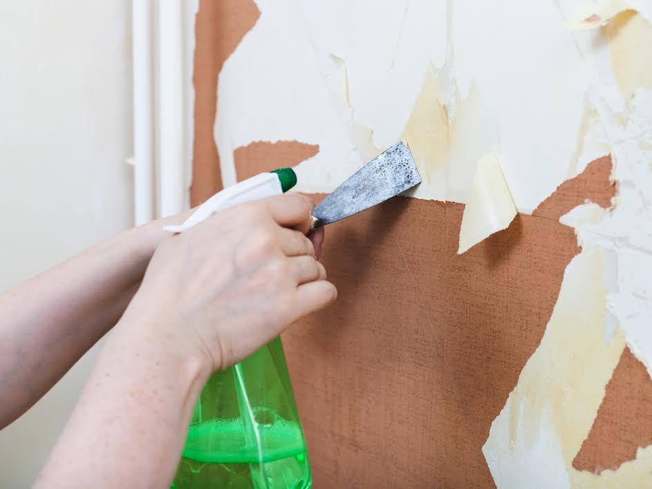 Spay бутылка и шпатель против стены обоями.