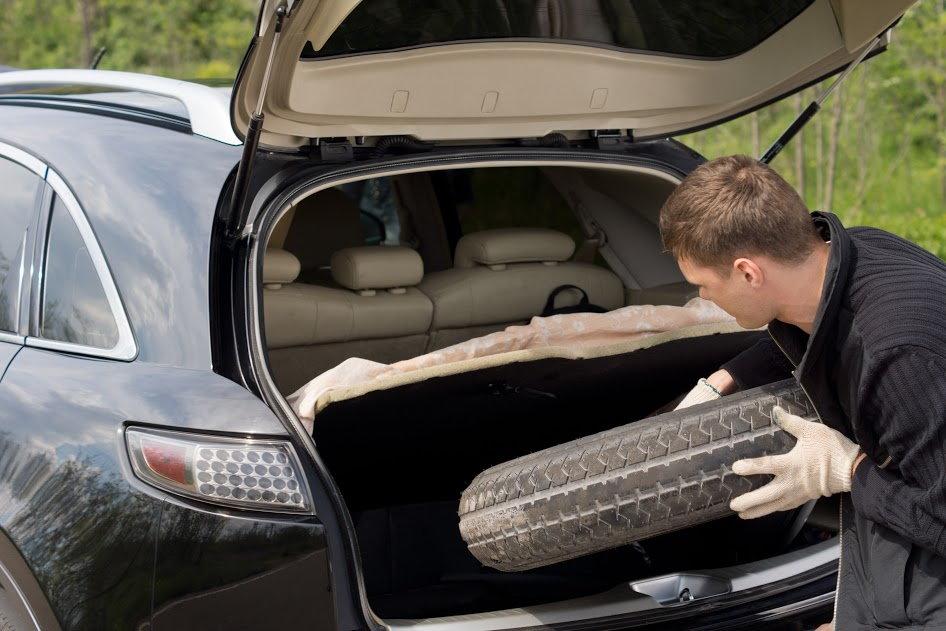 Мужчина снимает запасное колесо с багажника автомобиля.