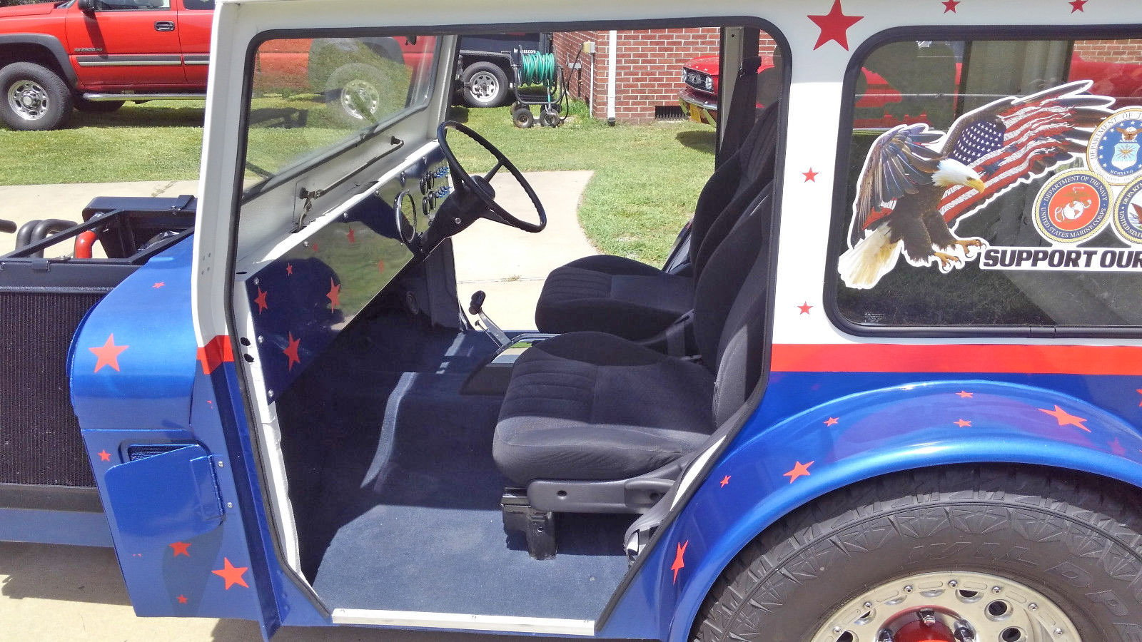 There is a Red White and Blue Postal Jeep with Two Motors