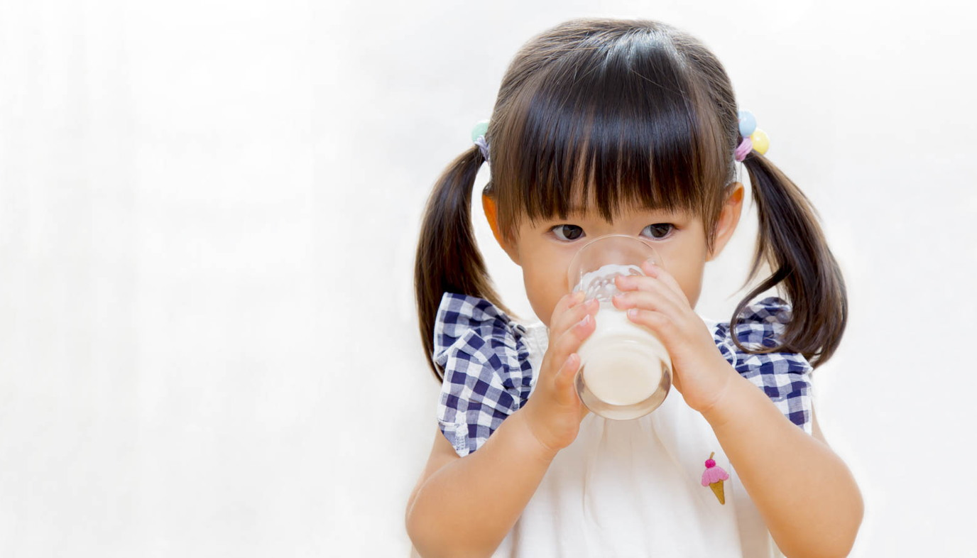 little girl drinking a glass of milk