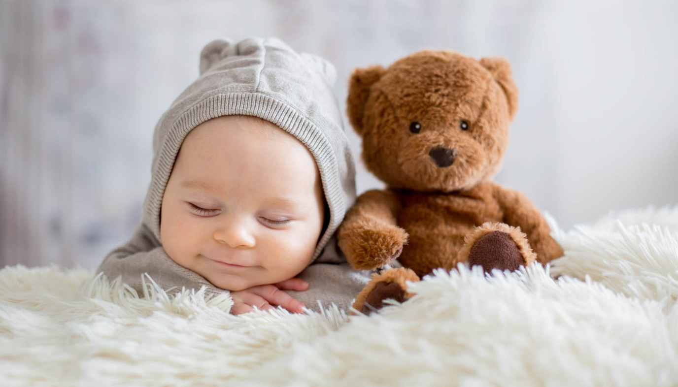 baby resting on his hands next to a teddy bear