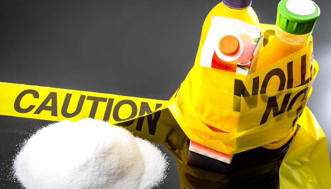 caution tape wrapped around sugary drinks