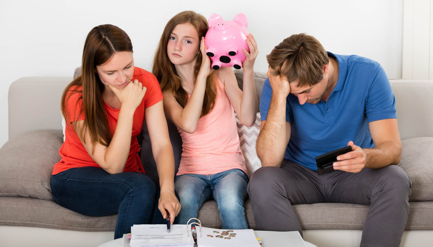 family sitting on the couch writing a budget with girl holding a piggy bank