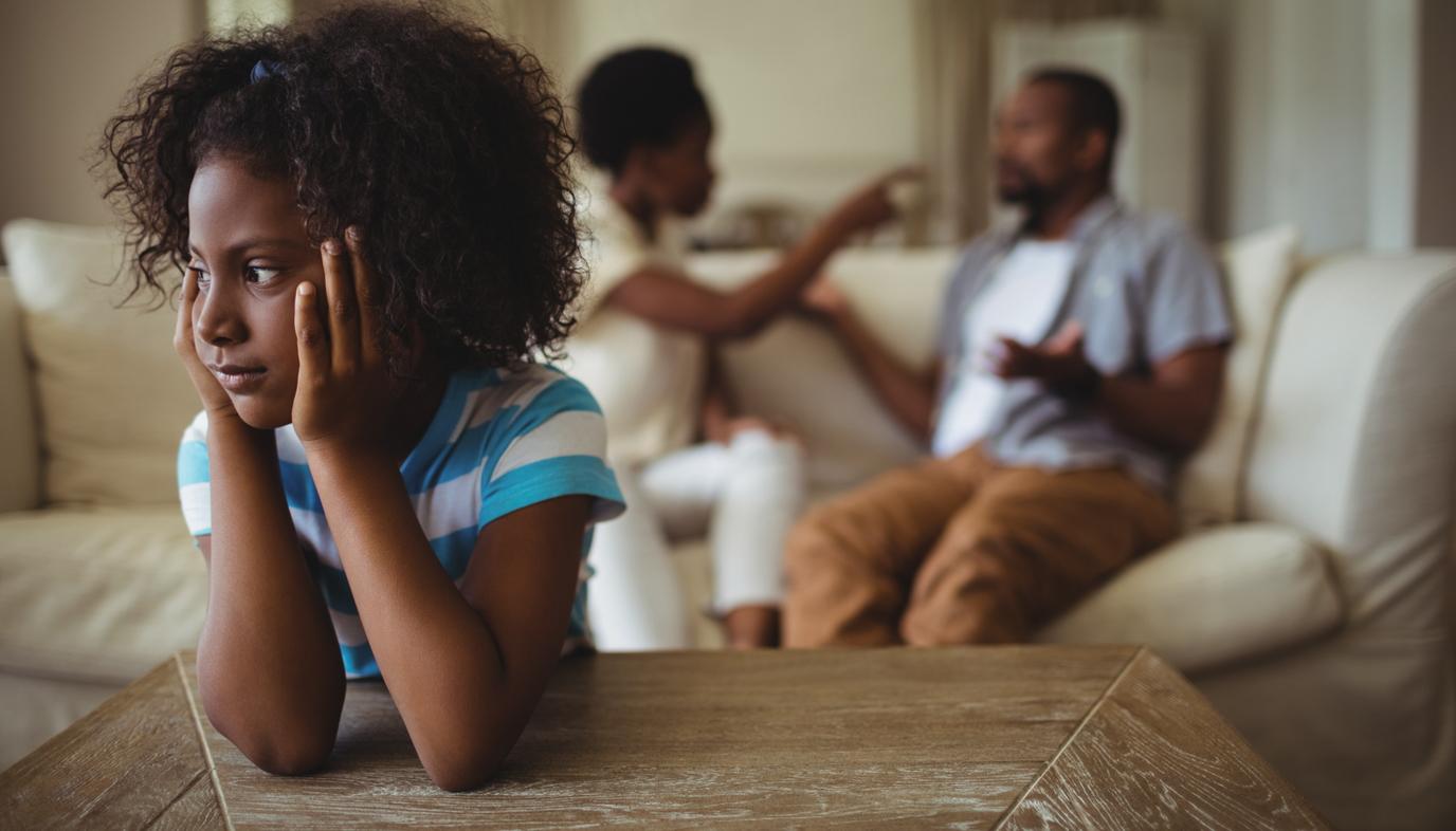 sad girl listening to parents argue