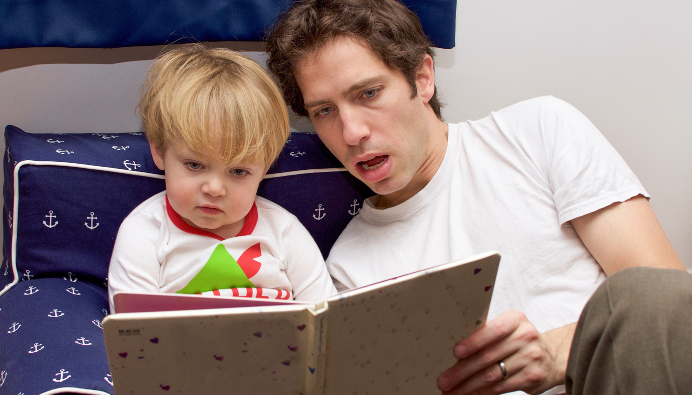 dad reading bedtime story to little boy