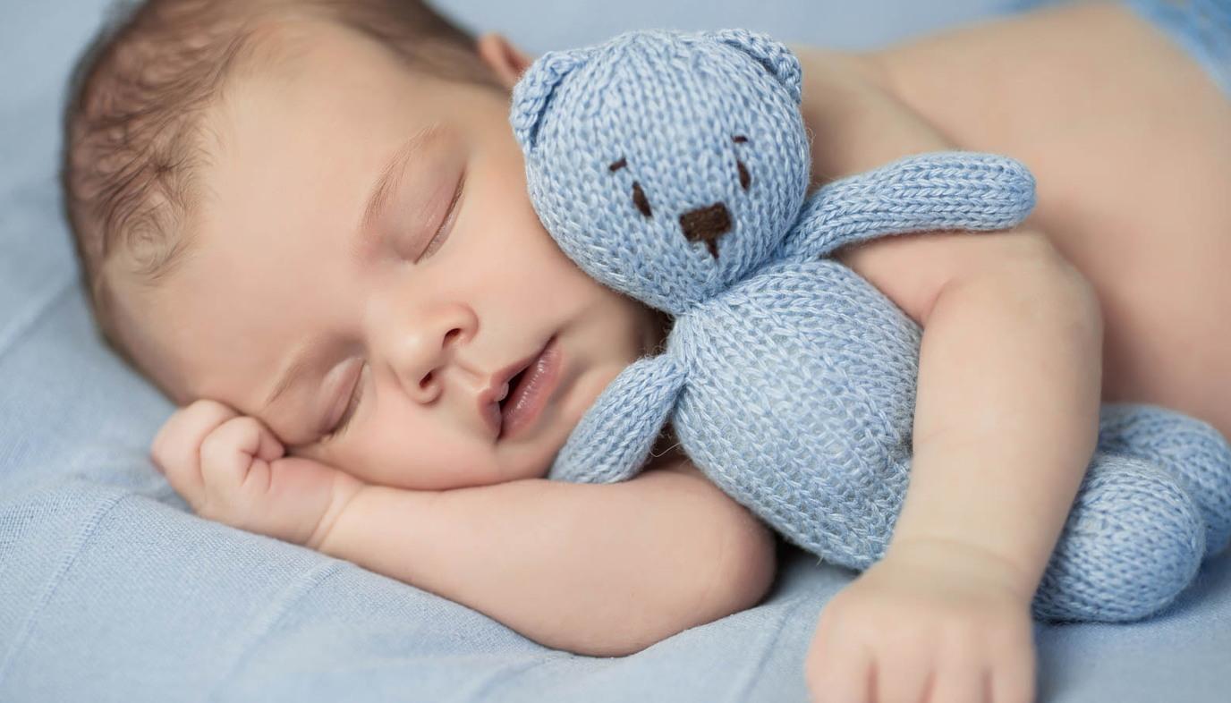 baby sleeping with blue teddy bear