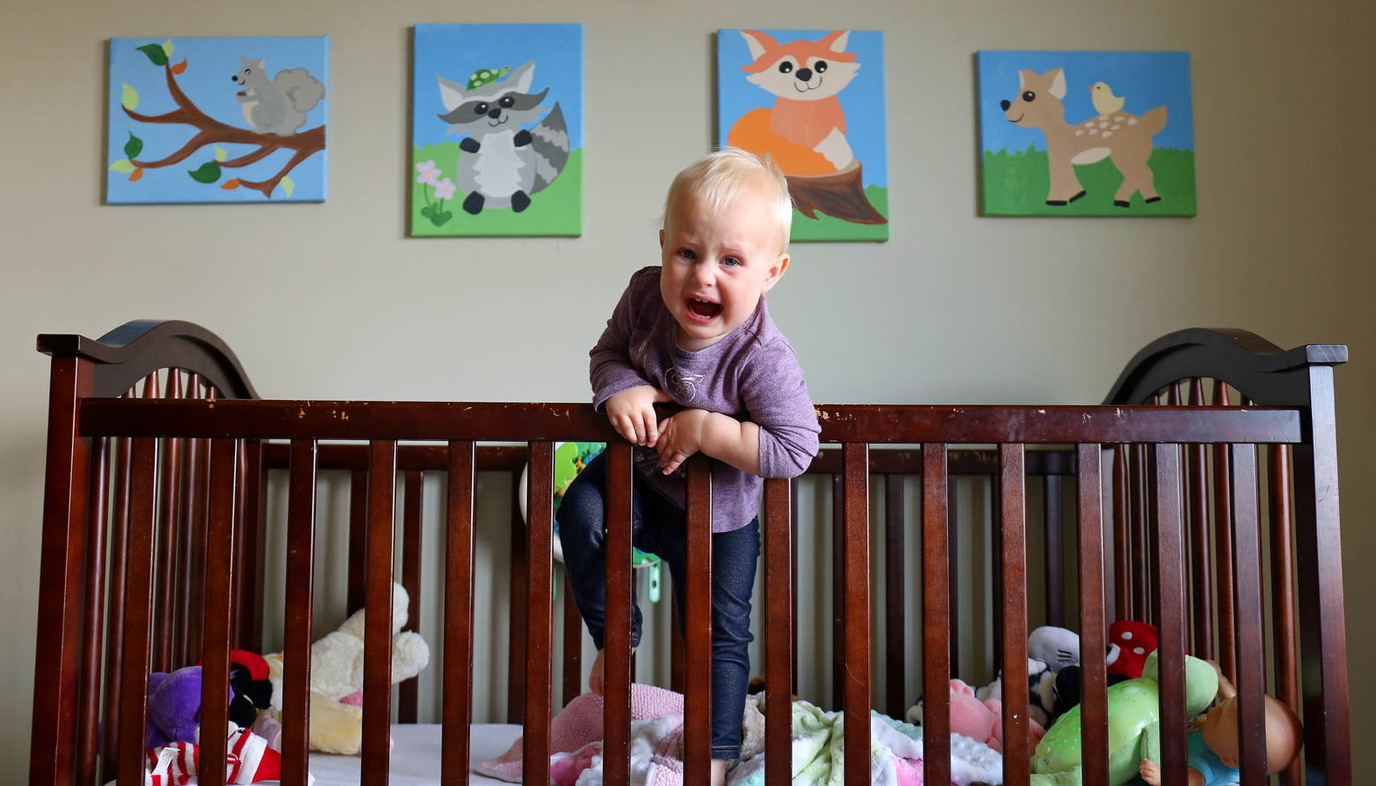 baby trying to get out of a crib and crying