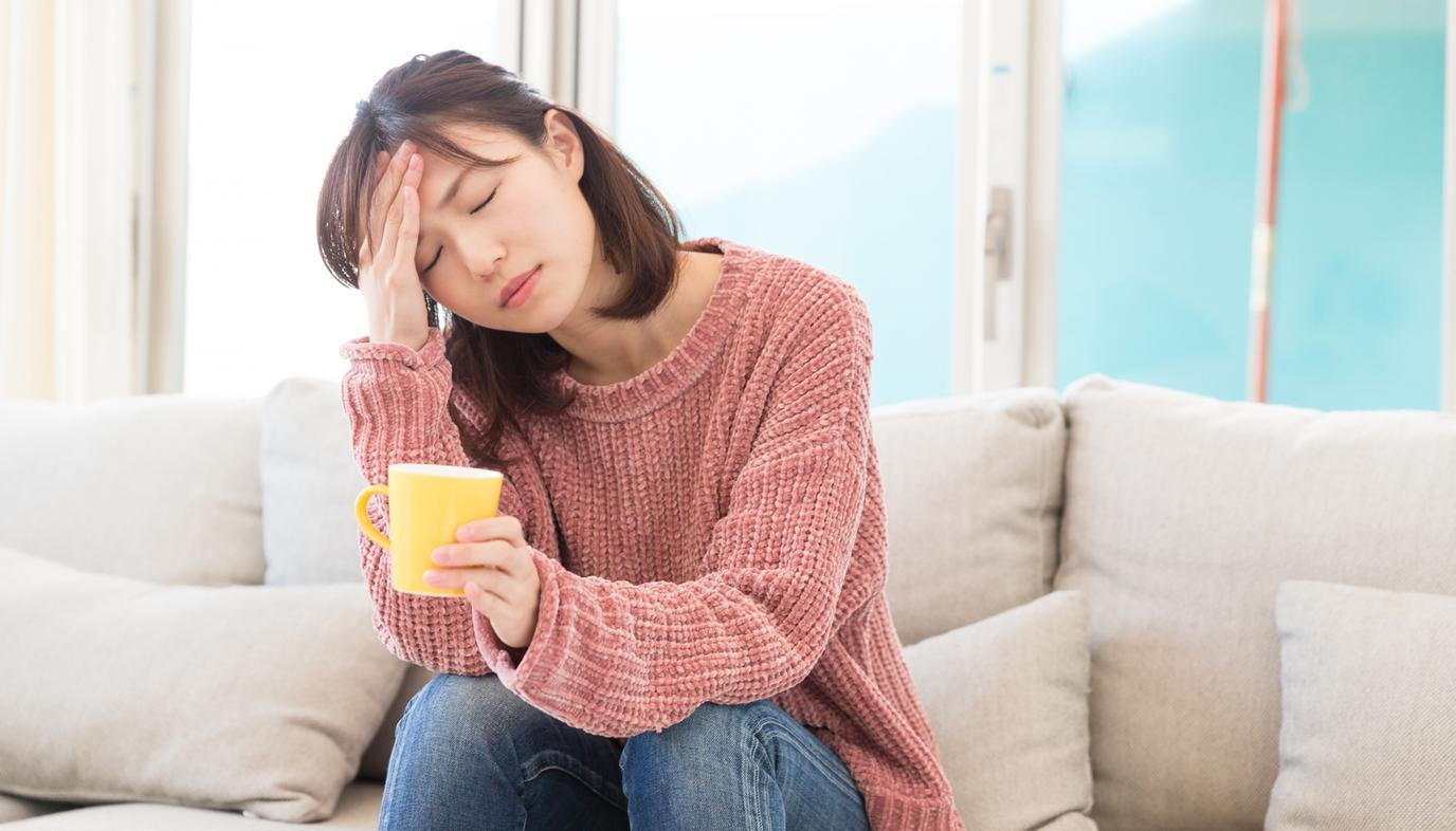 woman with headache drinking tea