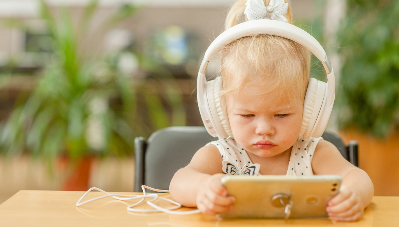 toddler wearing headset and watching video on smartphone