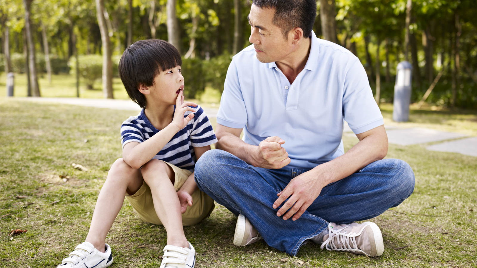 father talking to son at the park