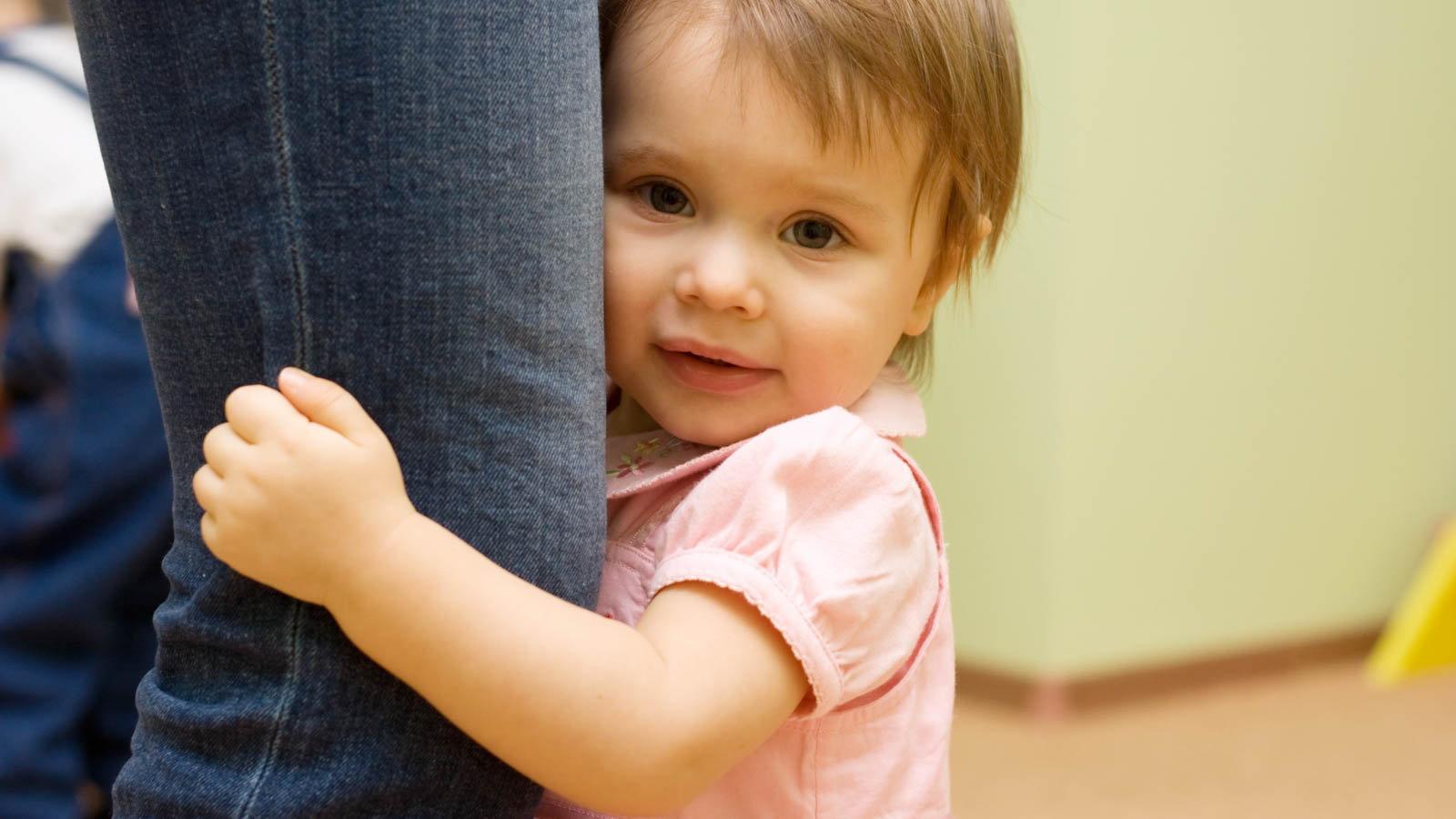 shy toddler holding leg