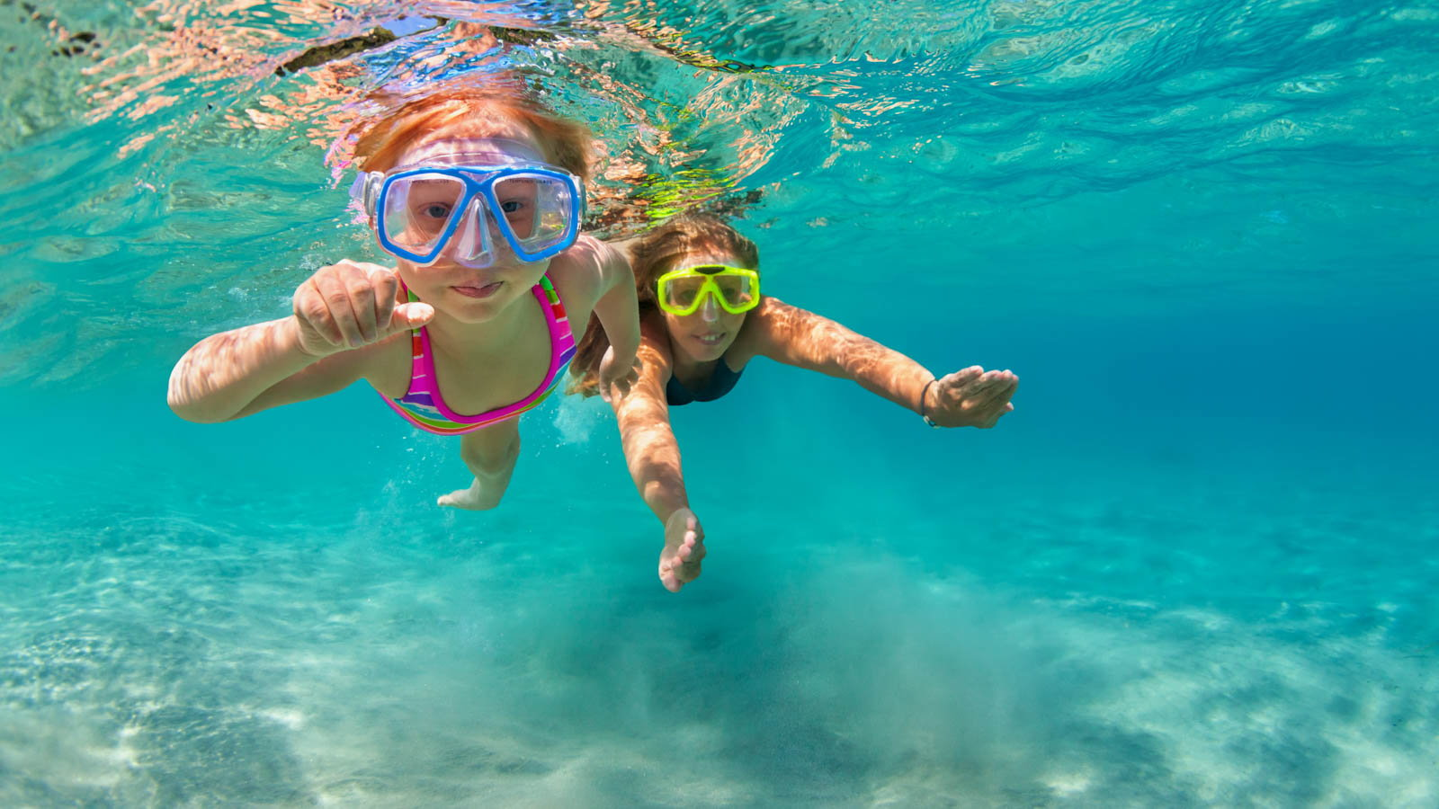 mom and child swimming with goggles on