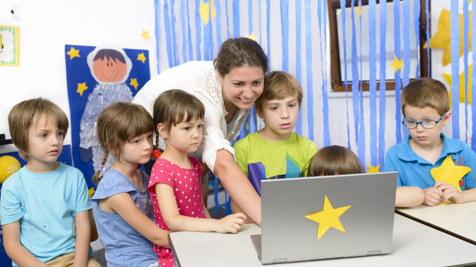 teacher and kids using laptop