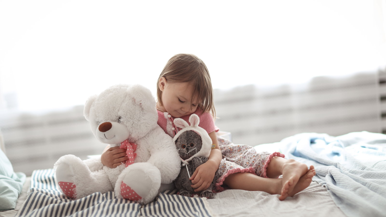 little girl in bed holding stuffed animals