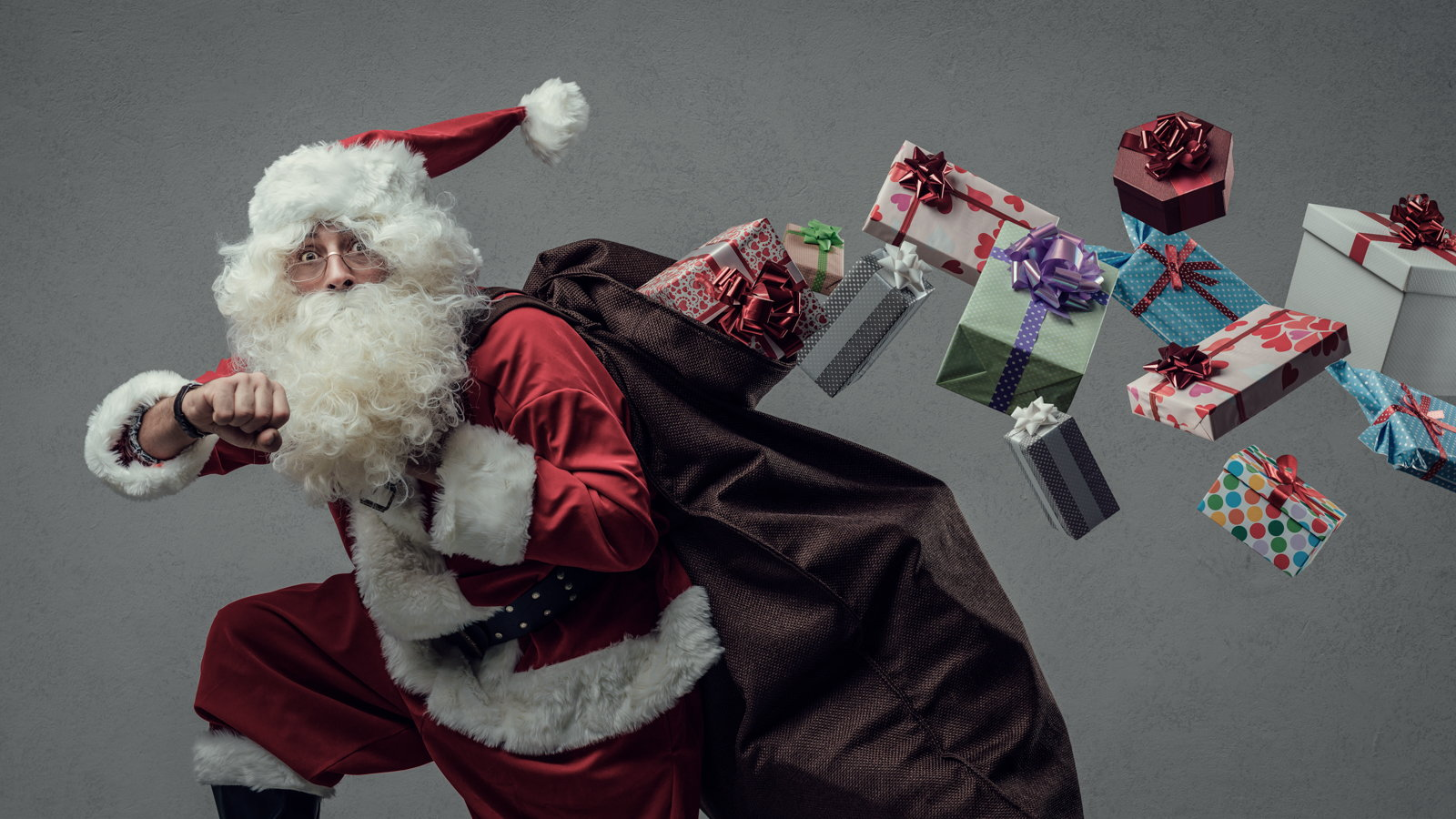 Santa Claus running with gifts flying out of bag
