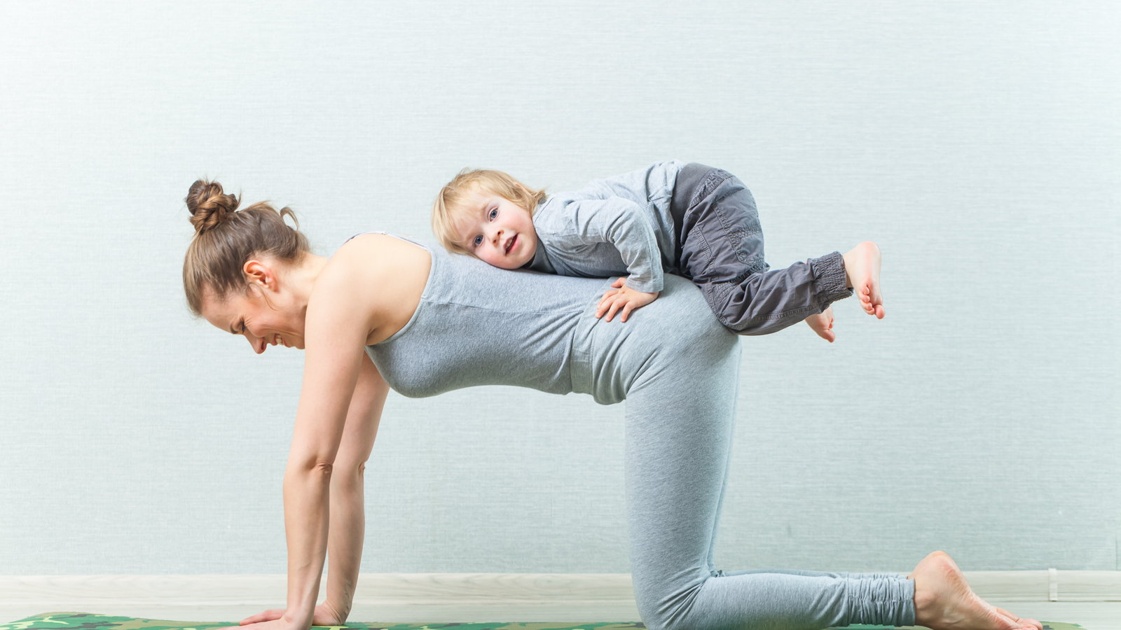 mom doing yoga with toddler