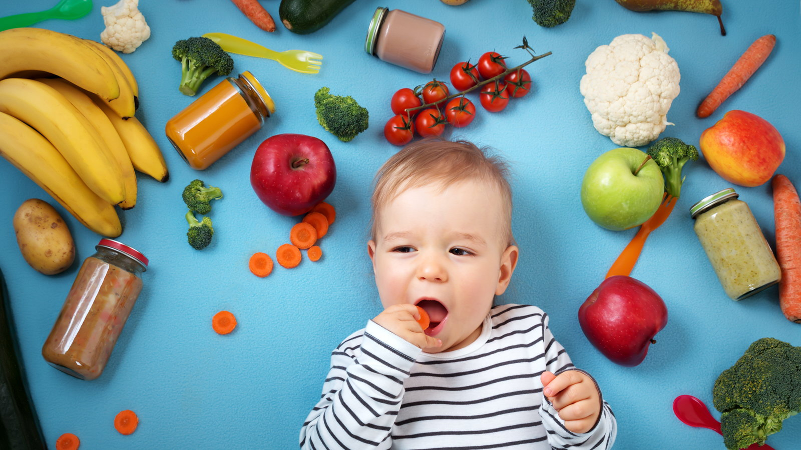 baby surrounded by fruits and vegetables
