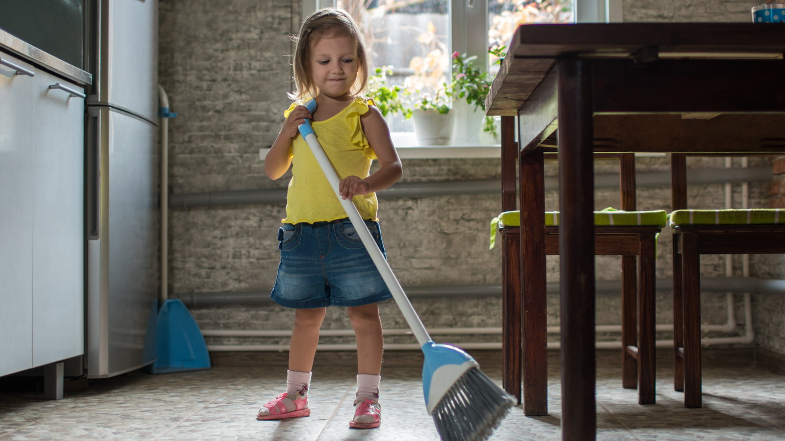 little girl sweeping kitchen