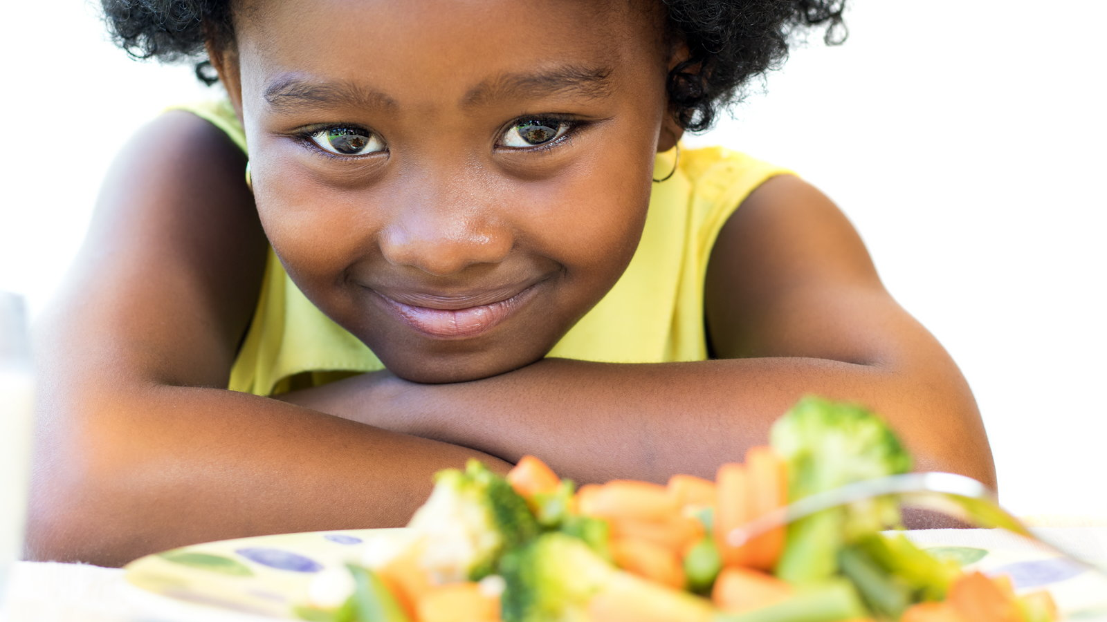 little girl with plate of vegetables