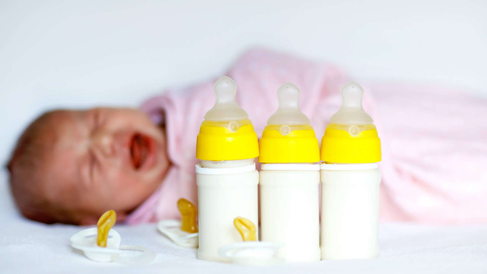 crying baby with bottles close by