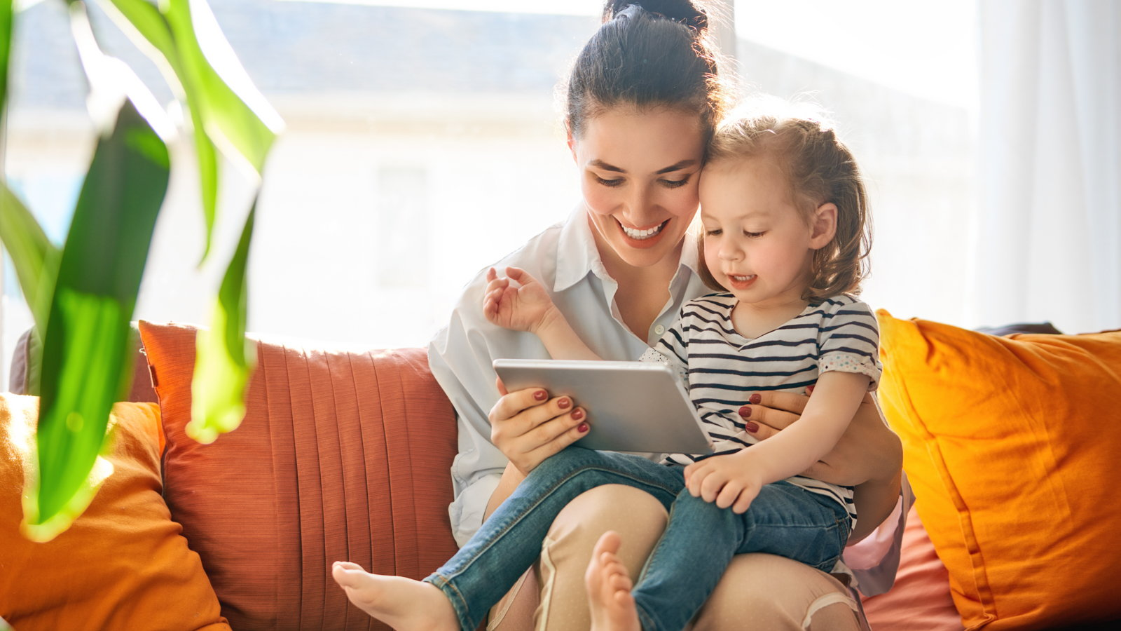 mom playing on tablet with daughter