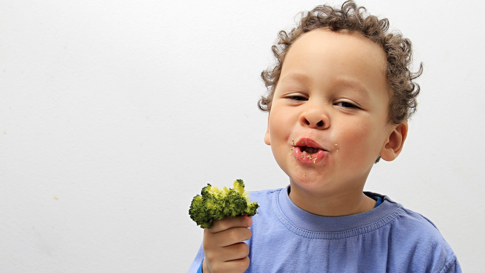 little boy eating broccoli