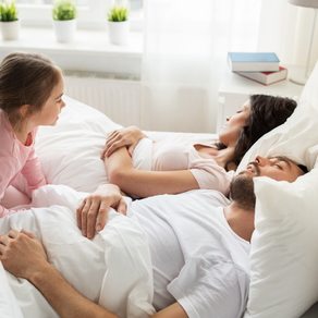 couple sleeping in bed with daughter crawling in the bed