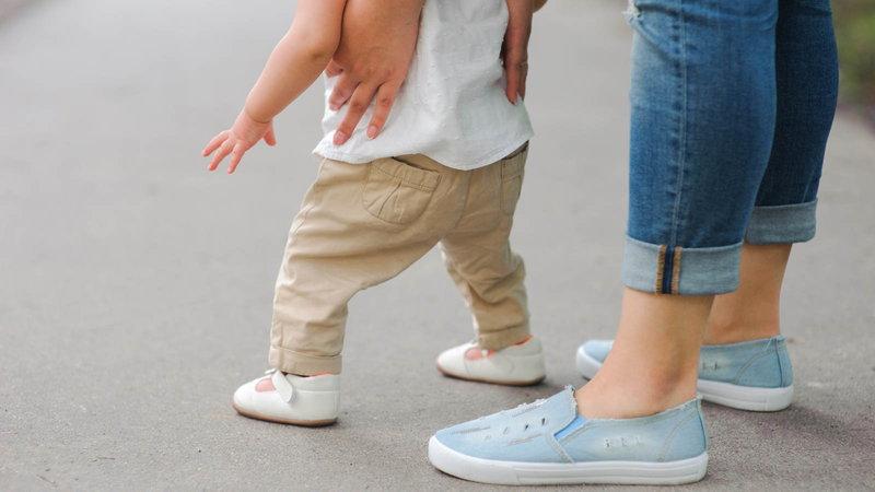 mom helping baby walk