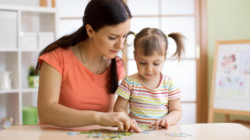 mom putting puzzle together with daughter