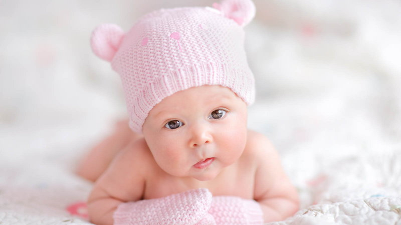 Baby wearing pink hat and gloves