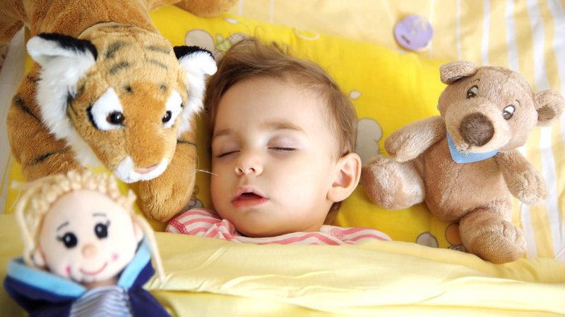 Baby sleeping with stuffed animals