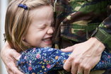 military personnel hugging their child