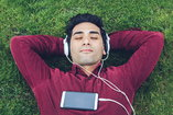 A recovering addict lies on the grass, as he listens music.