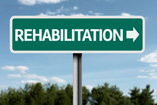 road sign pointing towards a rehab center