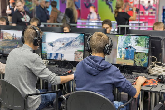 Two boys sit playing video games at a convention, unaware of the dangers of gaming disorder.