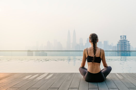 A woman sits by a pool practicing mindfulness techniques to stave off cravings for drugs and alcohol.