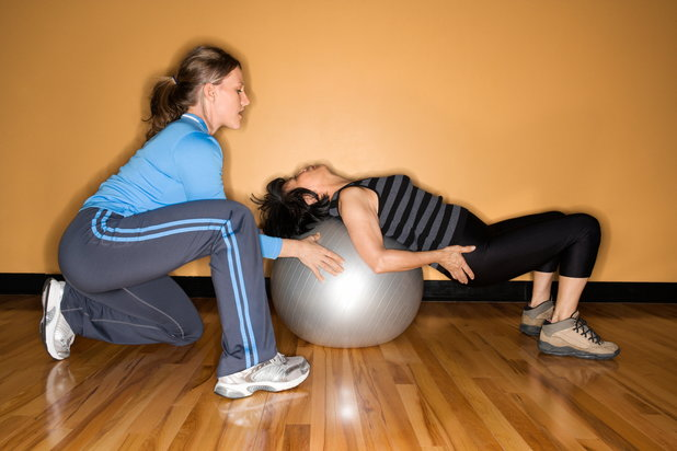 Woman exercises with physical therapist despite pain