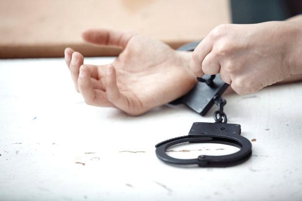 hands unlocking handcuffs