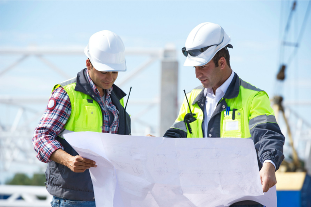 two men in construction gear looking at blueprint