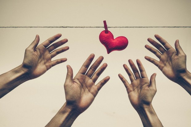 4 hands reaching for a heart