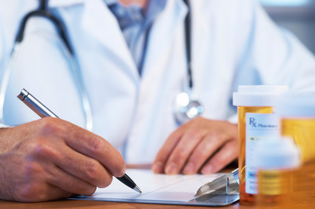 doctor writing up prescription